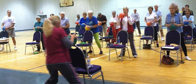 Seniors exercising with chairs and balls